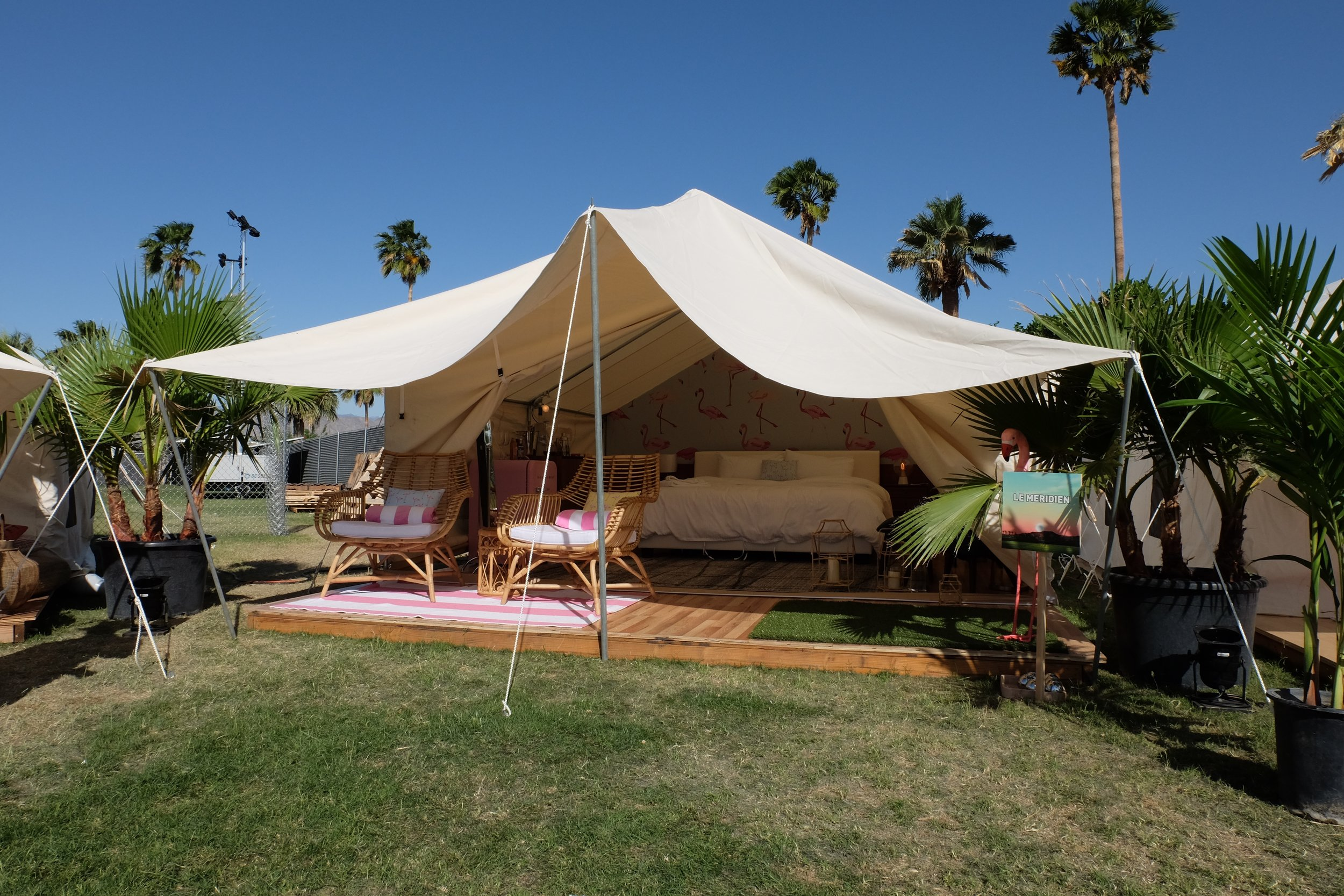 Image of an open tent with a bed and two chairs underneath and a flamingo wallpaper behind the bed