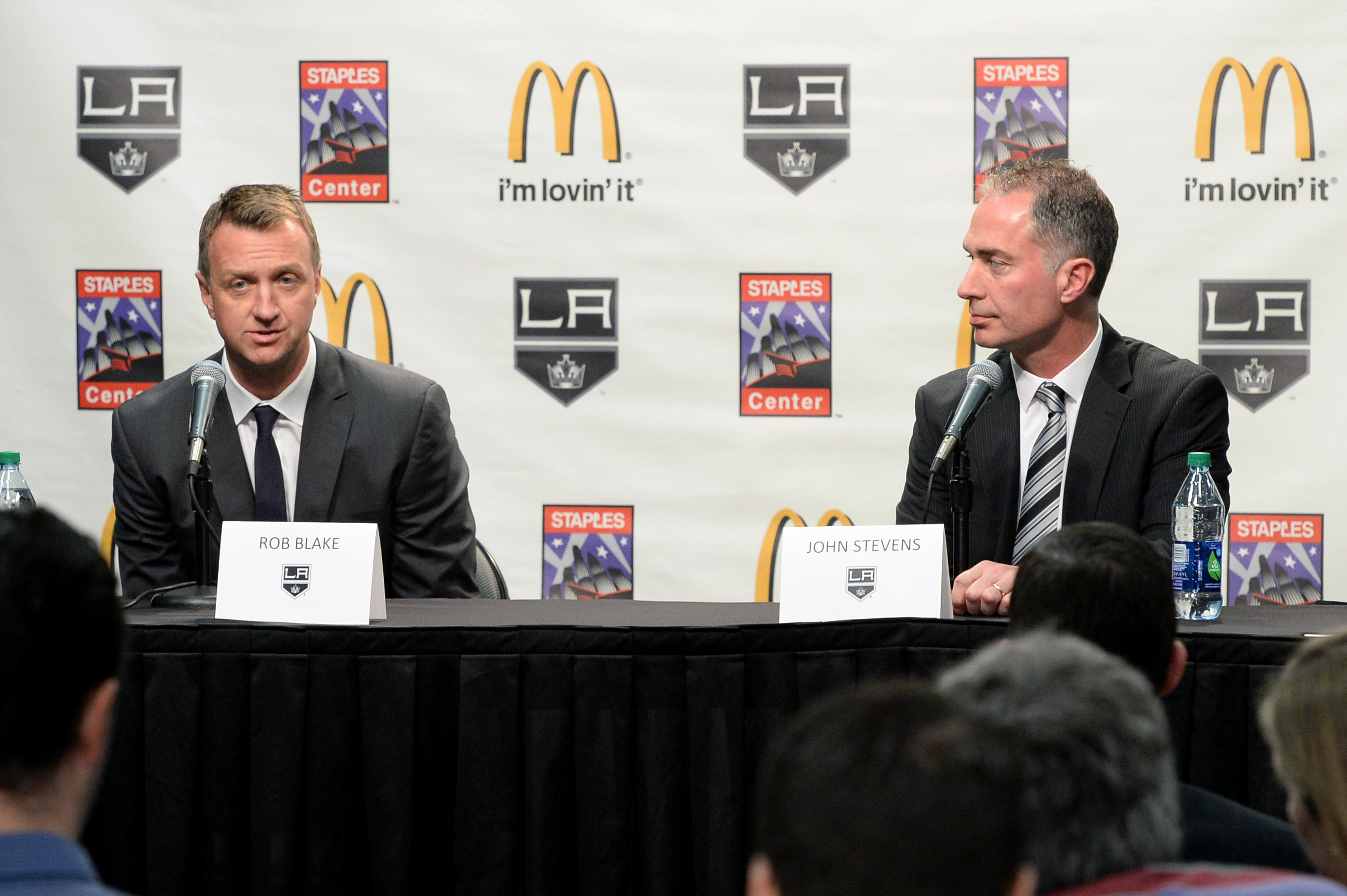 Image of Rob Blake and John Stevens at a LA Kings press conference with a LA Kings and McDonalds step and repeat behind them