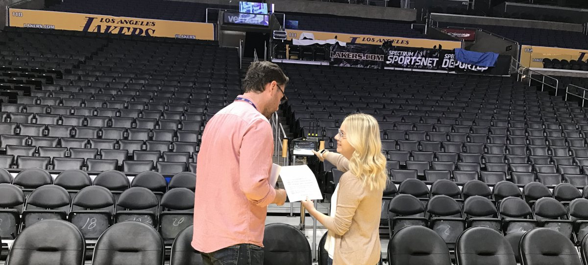 Two employees looking at a small screen in an empty arena
