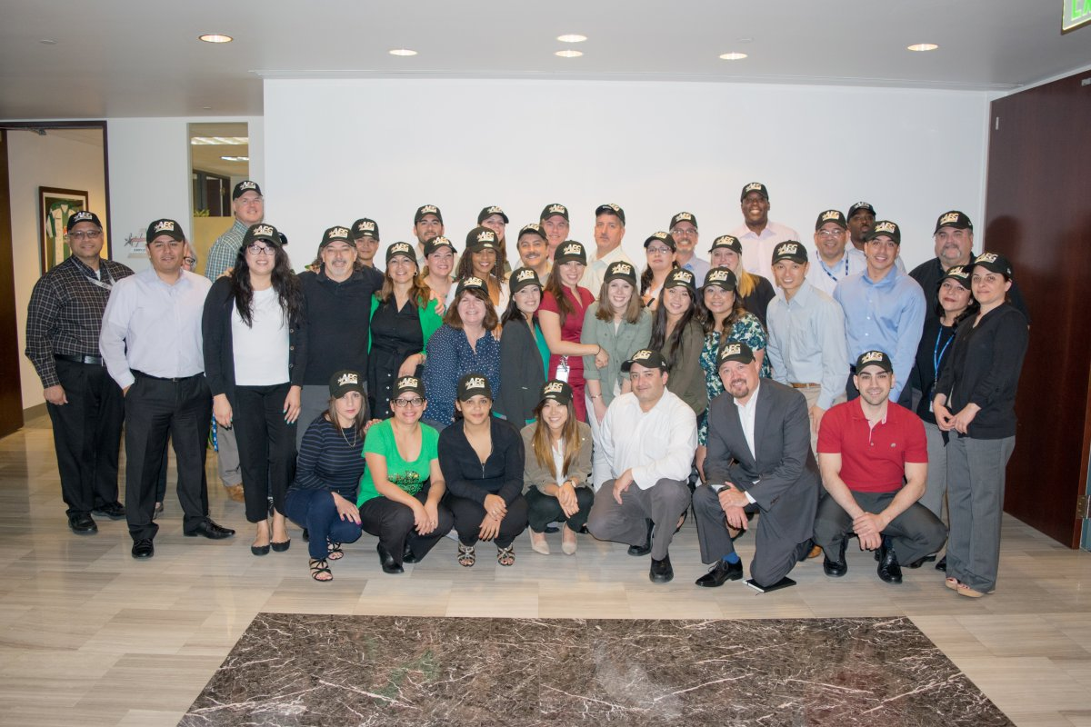 Group of AEG employees posing for a picture with matching AEG hats