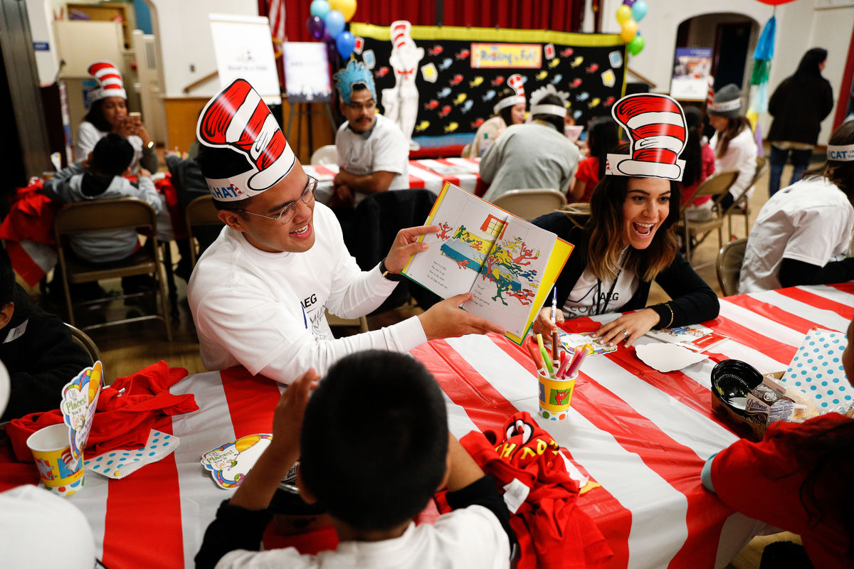 employee reading to a student in dr seuss hat