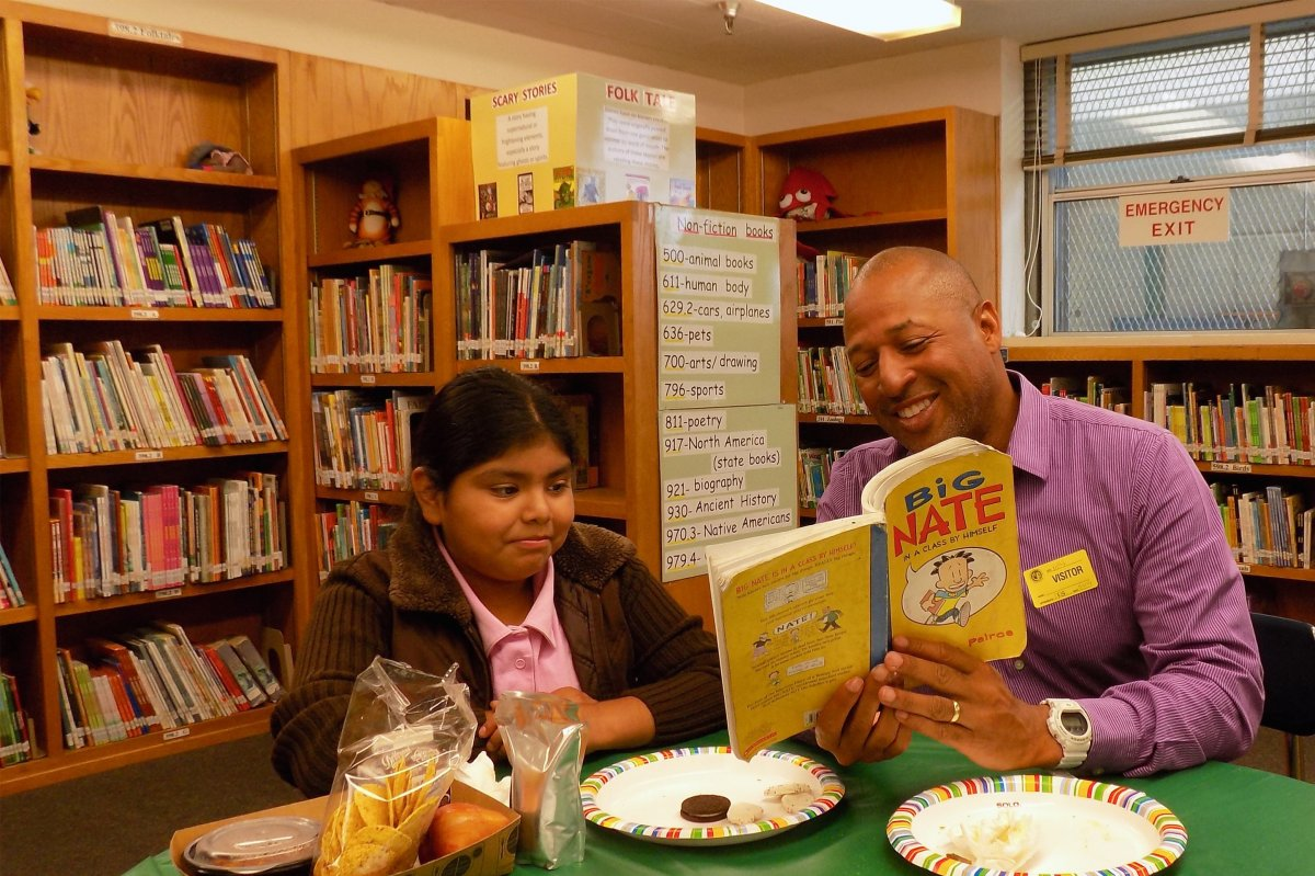 Employee reading to a student in a library