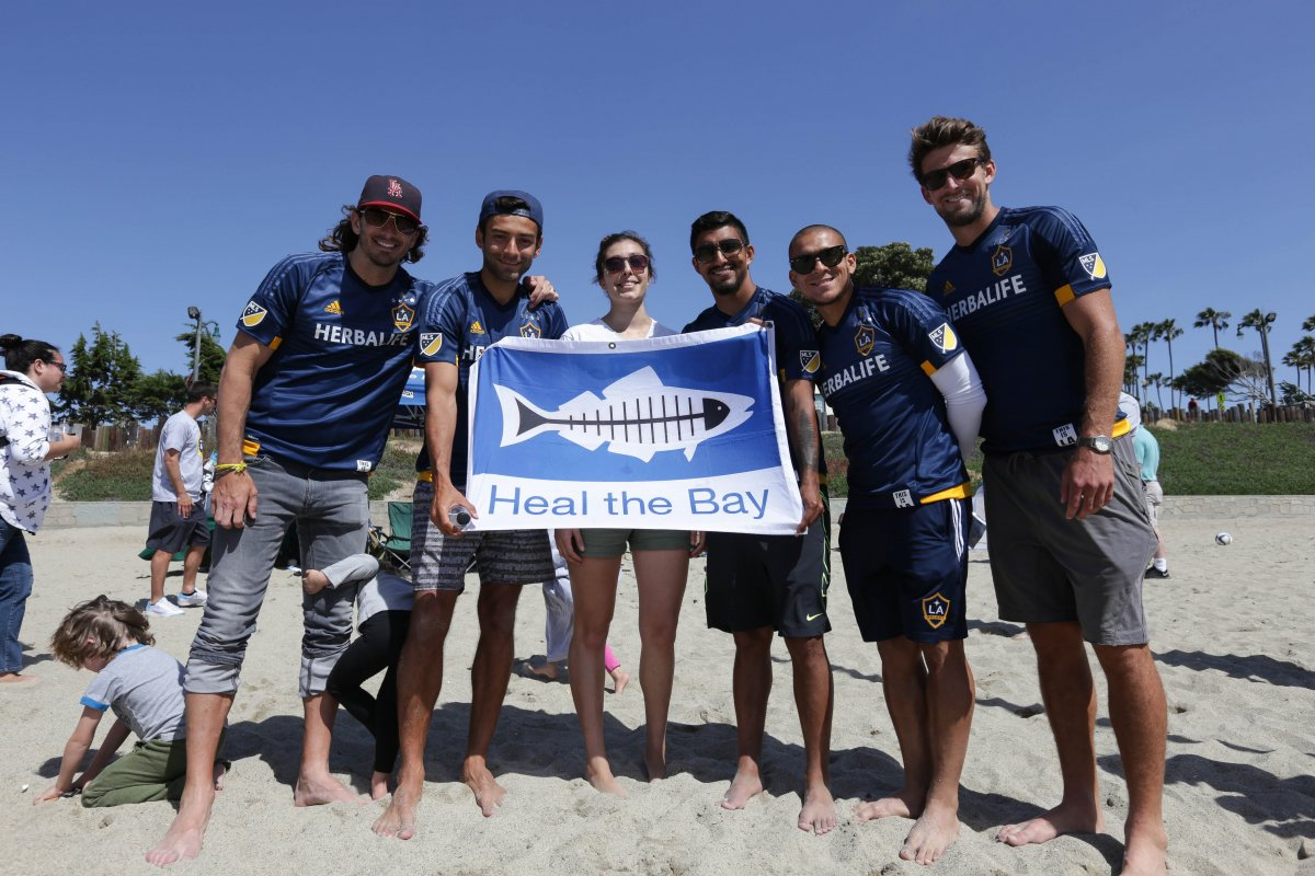 "Galaxy players and volunteers holding a flag that says ""Heal The Bay"" on the beach"