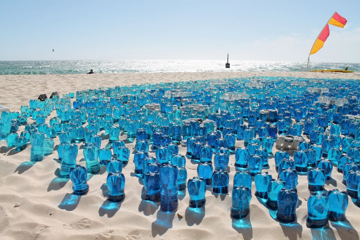 Hundreds of blue water bottles used as art upside down in the sand on the beach