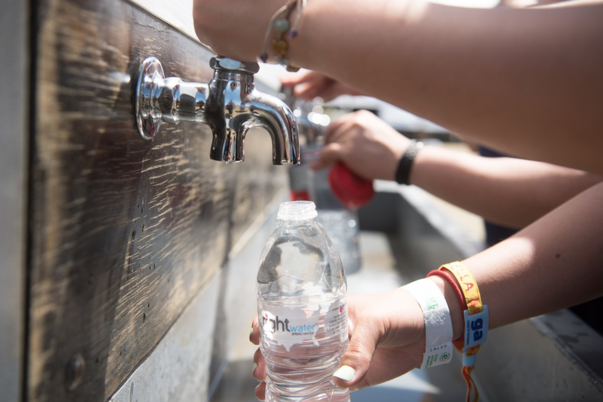 Close up of a festival goer refilling her plastic water bottle with water