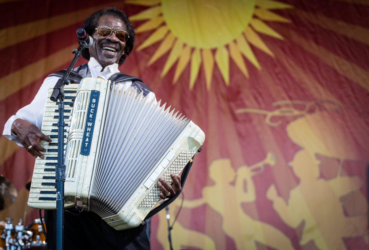 Image of a performer named Buckwheat on stage at New Orleans Jazz Fest playing the accordian