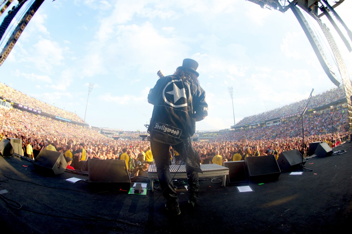 Image of the back of a performer playing the guitar to a crowd during the day at Rock on the Range