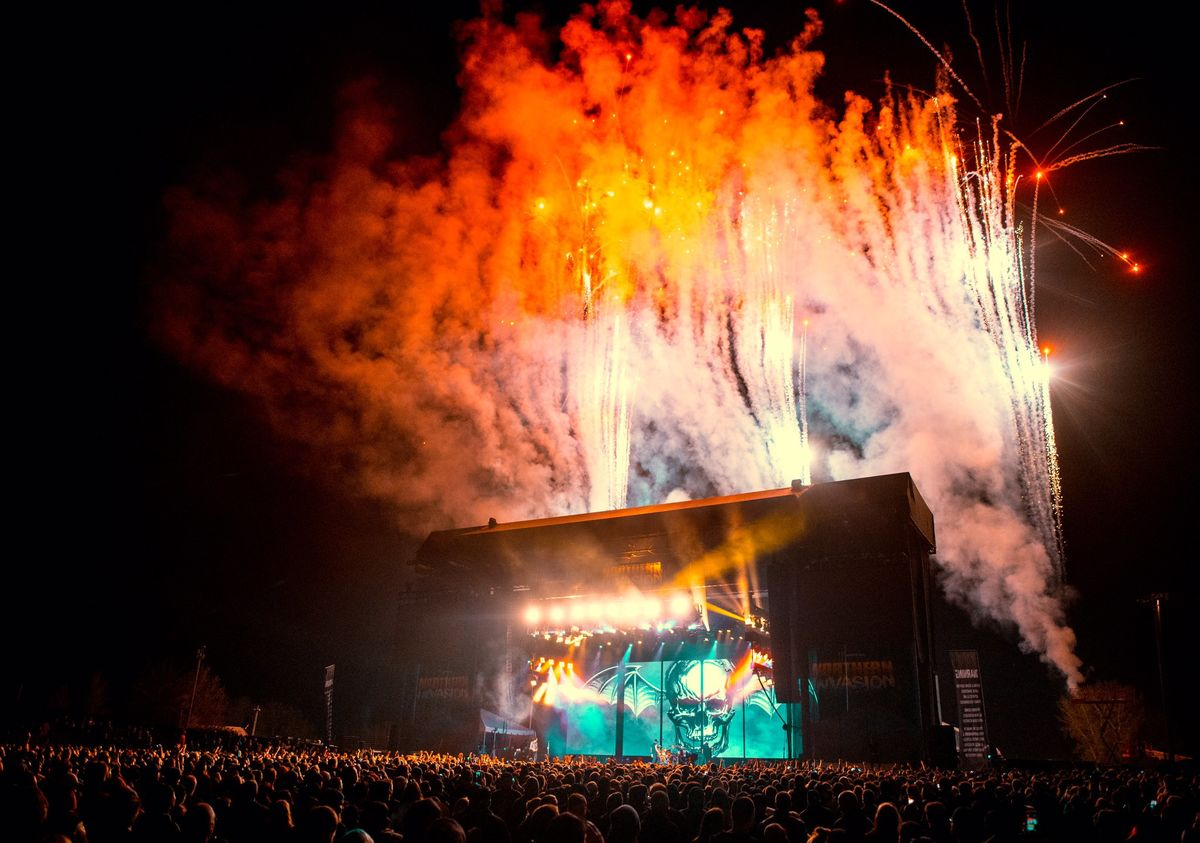Image of stage at night with fireworks behind it