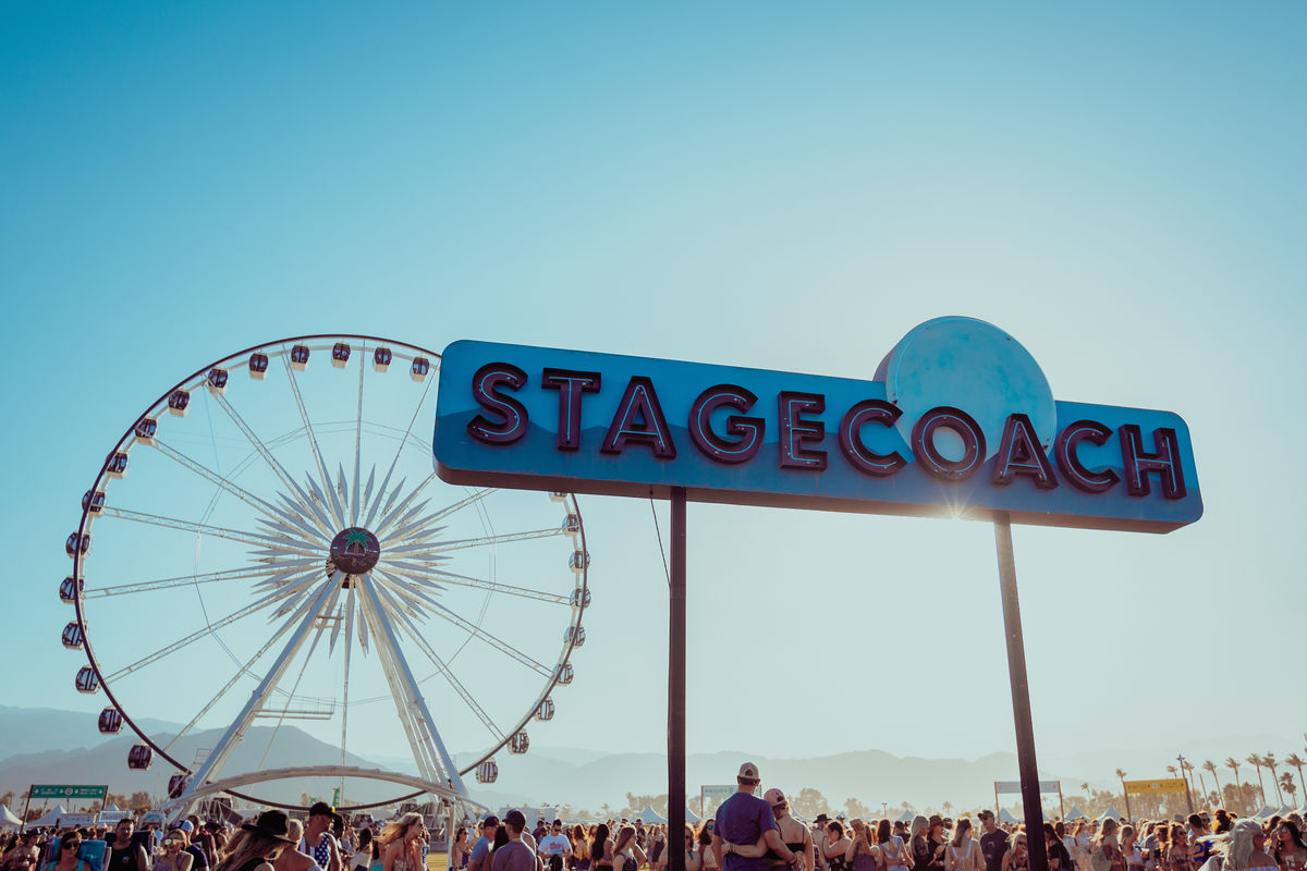 Image from behind of a performer playing the guitar and jumping in the air with the crowd and ferris wheel in front of him at Stagecoach