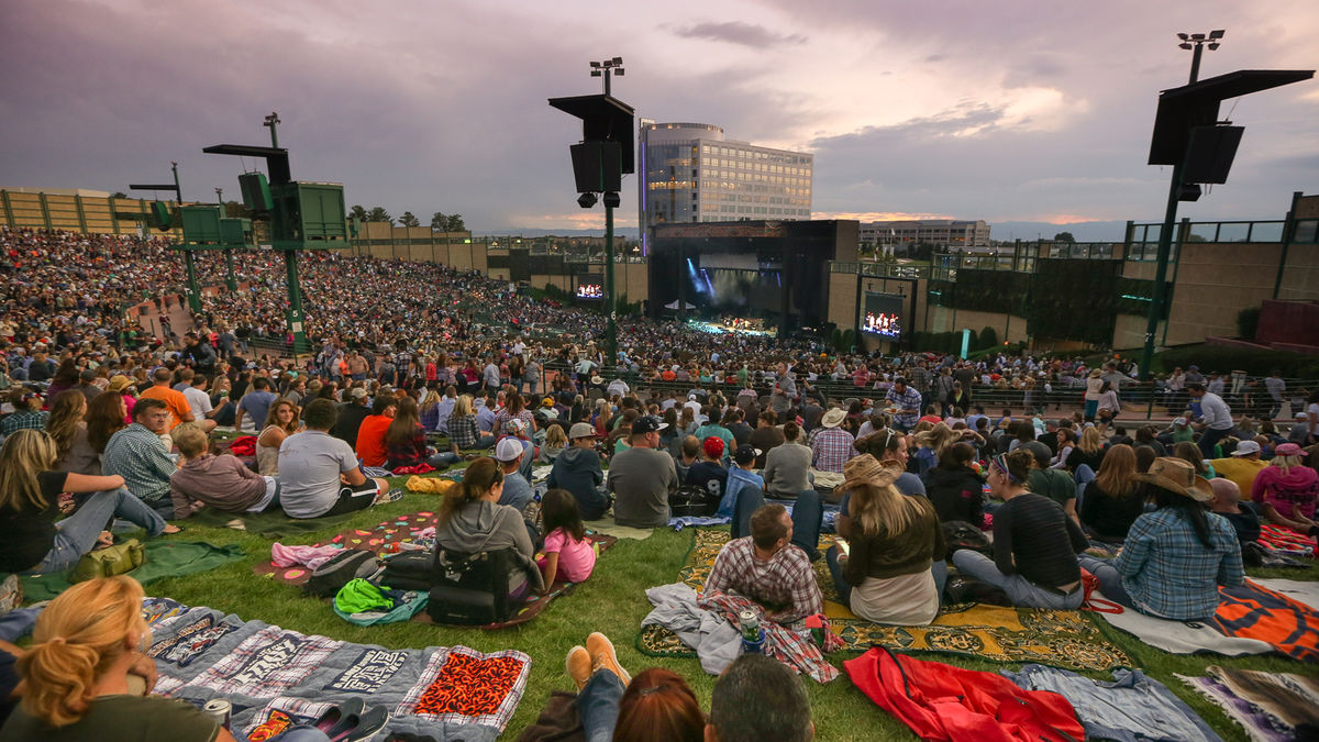 Image of stage from back of crowd with guests sitting on blankets on the field