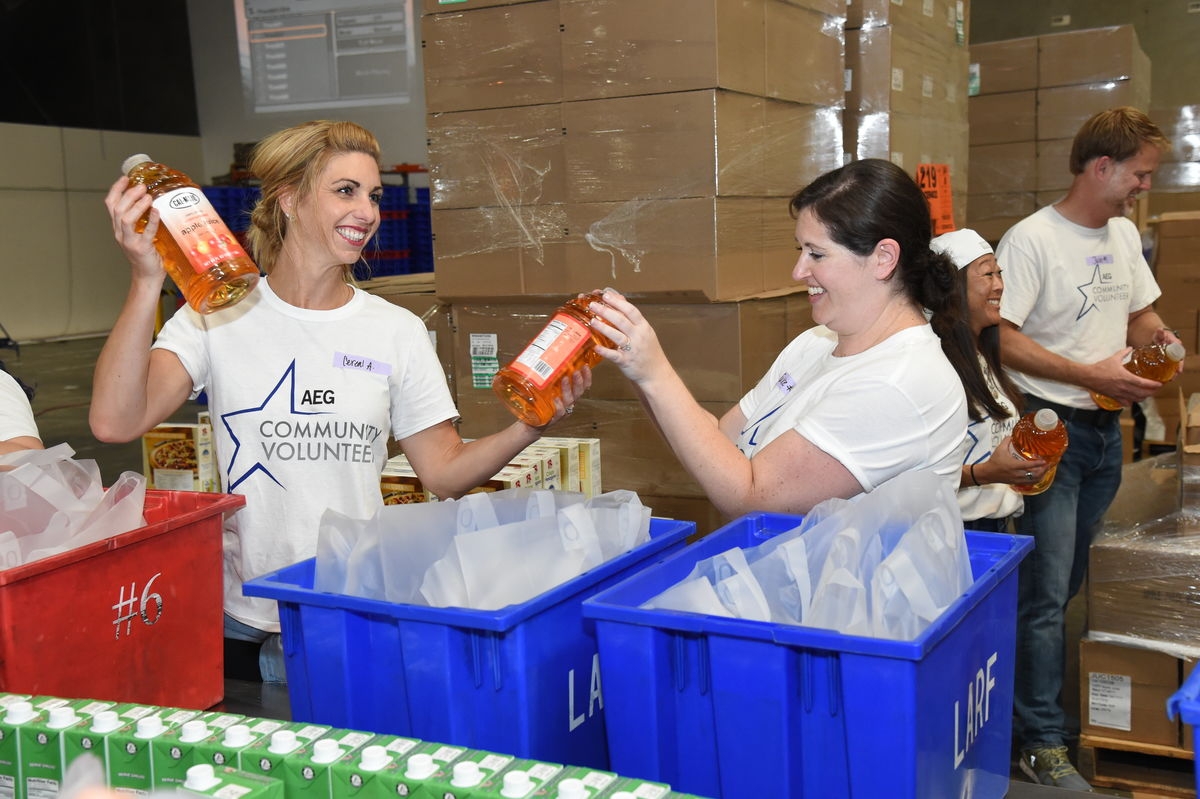 AEG employee volunteers add apple juice to food kits on the assembly line at the Los Angeles Regional Food Bank in Commerce, Calif. on Aug. 29, 2017. Throughout the day AEG employees prepared more than 1,400 food kits to be distributed to seniors in the greater Los Angeles area.