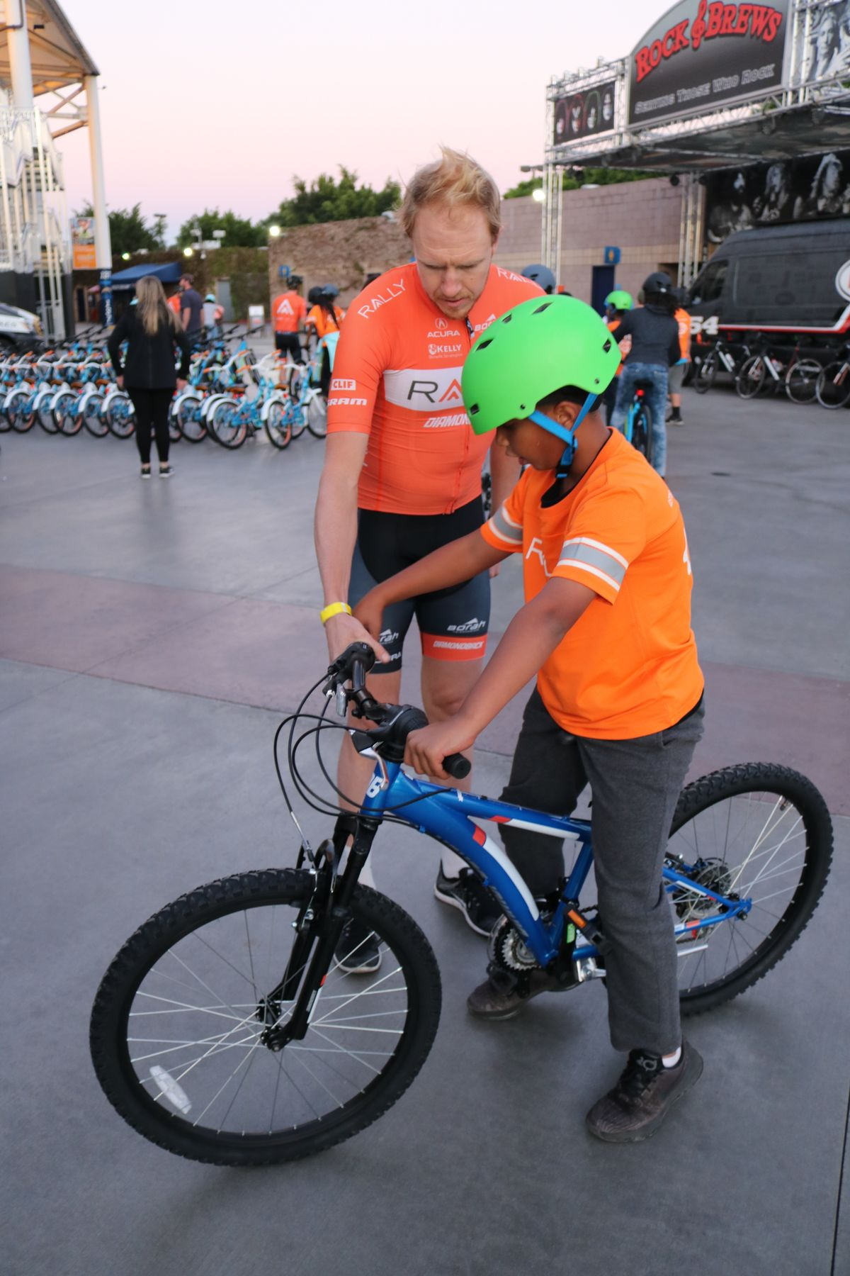 A professional rider from Rally CyclingSM fits boy from the Boys & Girls Club of Carson for a bike at Rally Health's Holiday Bike Build at StubHub Center on December 5, 2017.