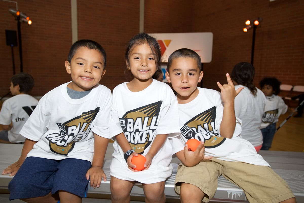 Three youth participants pose for a photo during the LA King's Ball Hockey Clinic at a YMCA in the greater Los Angeles area.