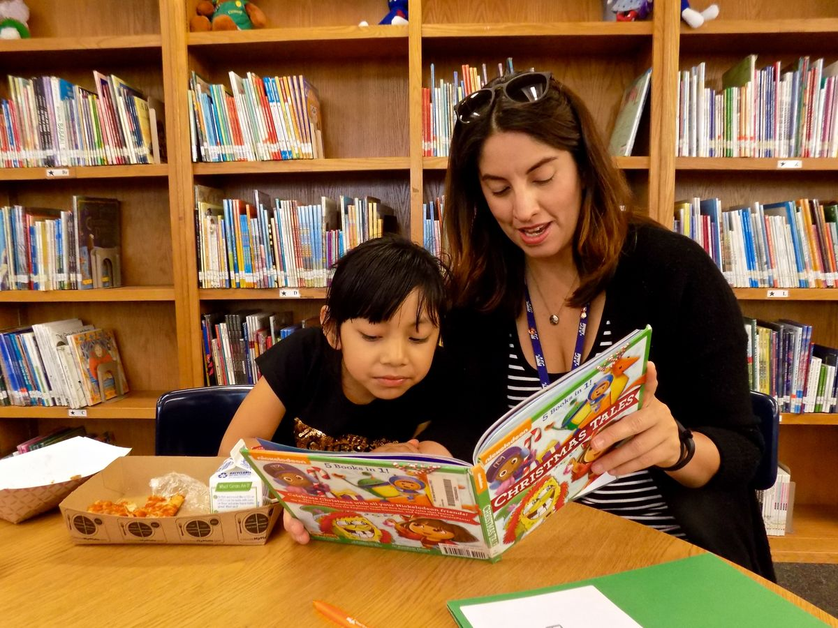 AEG's Jatzin Alvarado reads to a student at Tenth Street Elementary in Pico-Union as part of the Read to a Child Lunchtime Program.