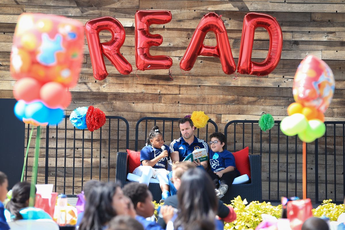 LA Galaxy President Chris Klein (center) reads Dr. Seuss' Hop on Pop with elementary students at the Read Across America Day Celebration at StubHub Center on March 1, 2018.