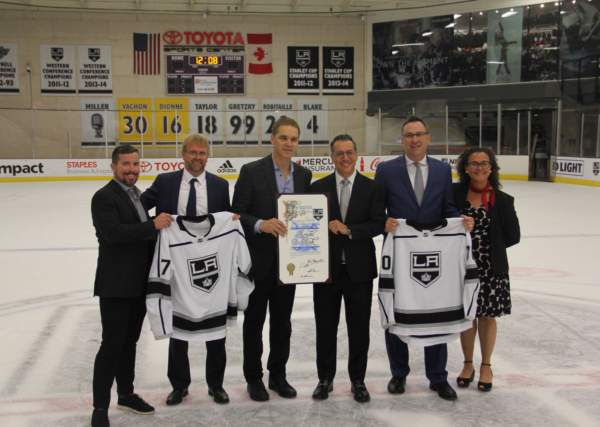Los Angeles Kings President and Hockey Hall of Famer Luc Robitaille (left-center) and Councilmember Bob Blumenfield (right-center) pose for a photo on the ice of Toyota Sports Center with members of the City of Los Angeles and other officials to celebrate the public-private partnership between the LA Kings and the City of Los Angeles to build and manage the Reseda Ice Rink