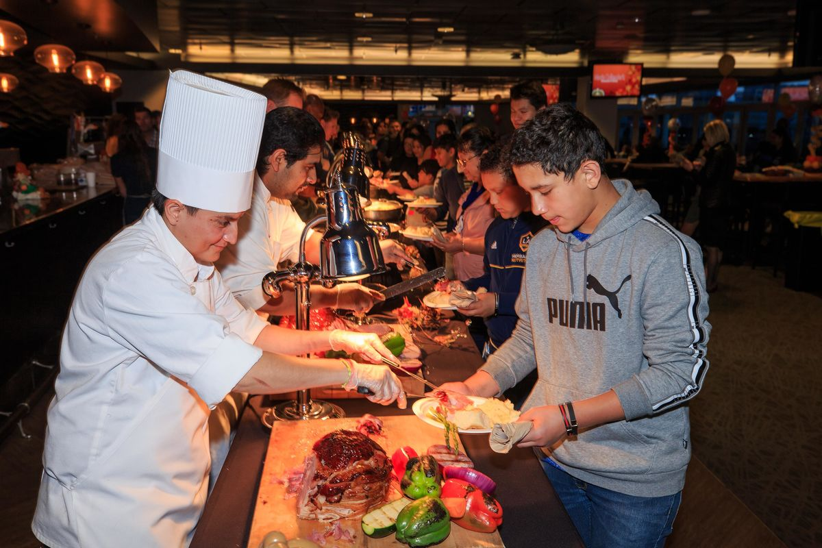 A chef carves a turkey and places a slice of meat on a child's plate during the buffet at the LA Galaxy and StubHub Center Foundations' Feast in Carson.
