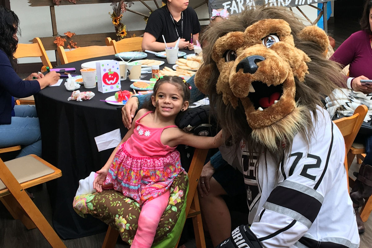 LA Kings mascot Bailey poses with a patient at the LA Kings Halloween party at the Los Angeles Ronald McDonald House on October 30, 2018.
