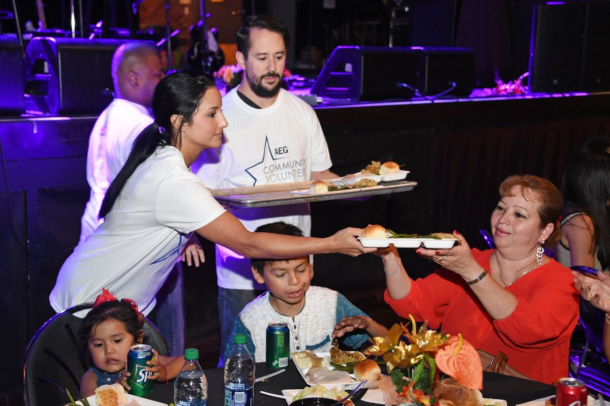 AEG community volunteers serve Thanksgiving meals to a family at The Novo at L.A. LIVE.