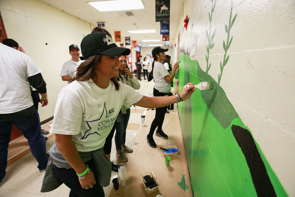 An AEG employee paints a design on the wall in a hallway at Magnolia Avenue Elementary for AEG's Annual Service Day.