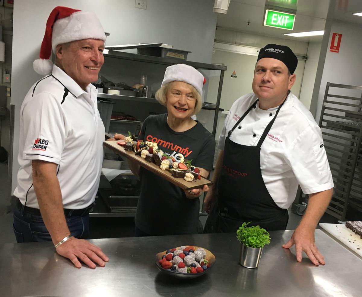 Suncorp Stadium General Manager Alan Graham (left), Communify Chair Carolyn Mason and O'Brien Group Australia Executive Chef, Bevan Campbell work in the stadium's kitchen to finalize the menu for the Christmas Day lunch.