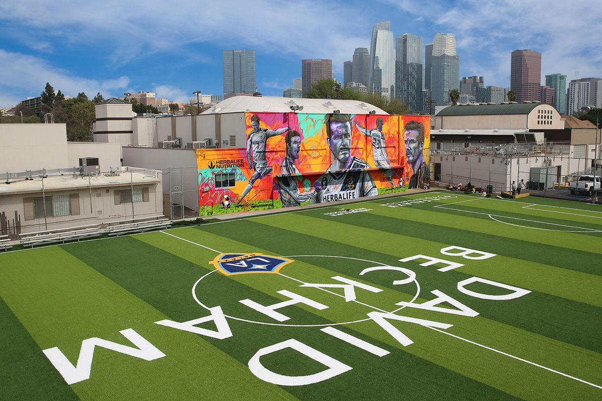 The David Beckham Community Field from an aerial shot features the LA Galaxy logo as well as a colorful mural of David Beckham on the side of the building.