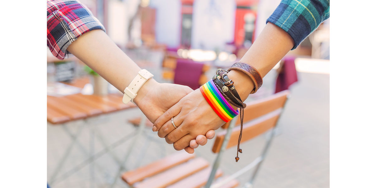 Two women hold hands - one with a Pride rainbow bracelet on.