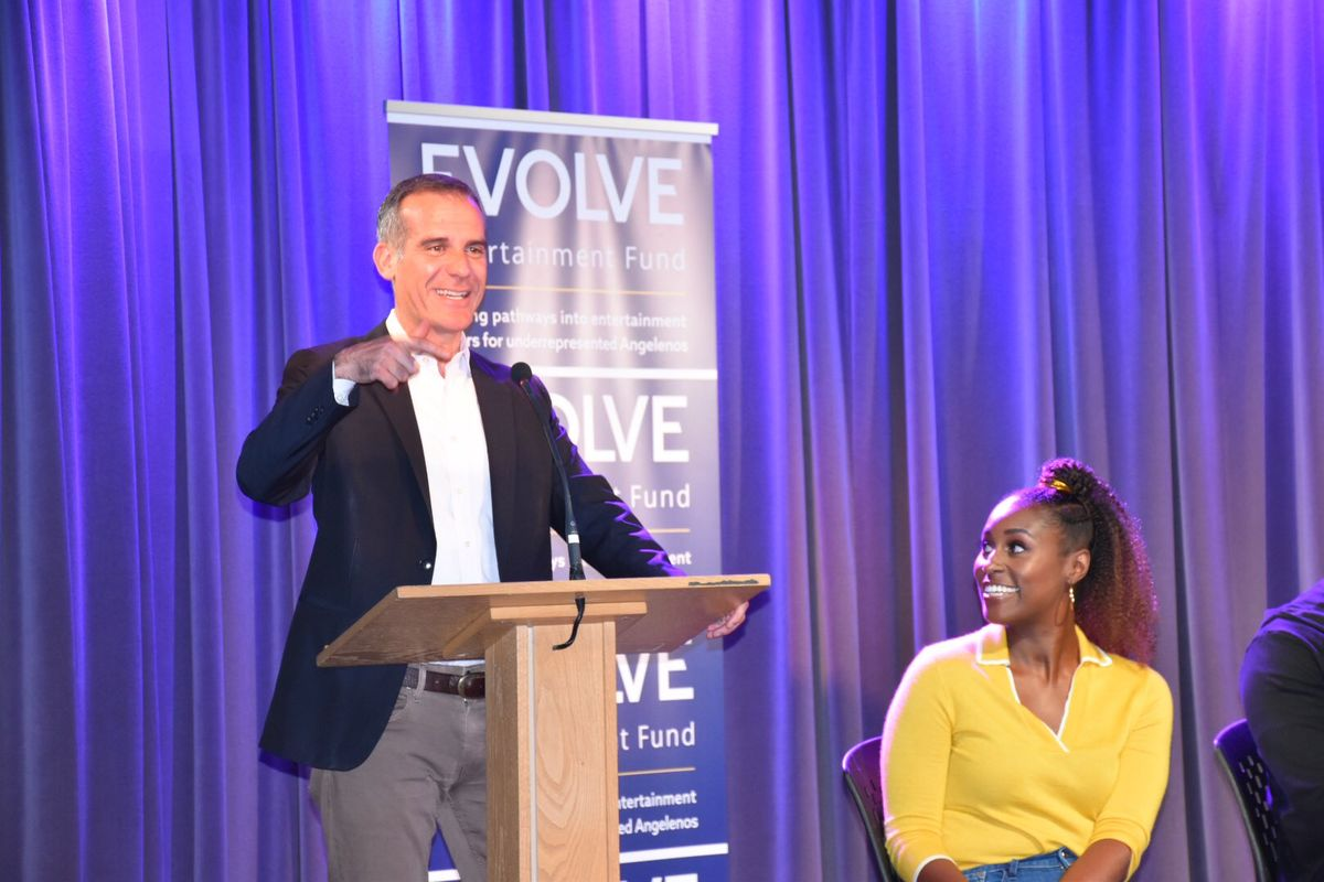 Mayor Eric Garcetti addresses the crowd from a podium as Issa Rae looks to him from stage during the Evolve Entertainment Fund 2019 Summer Kickoff at L.A. LIVE.