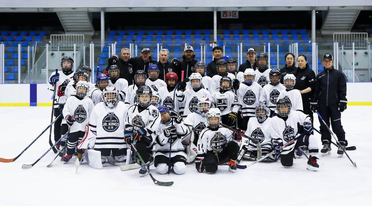 LA Kings hockey coaches and players ages 6-14 gather for a group photo on the ice in hockey gear.