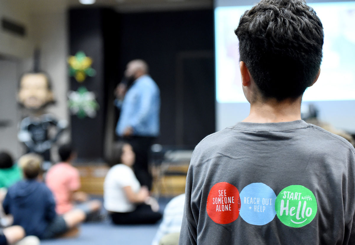 "A boy stands to speak during a Know the Signs class with the back of his shirt depicting ""See Someone Alone, Reach Out and Help, Start with Hello."""