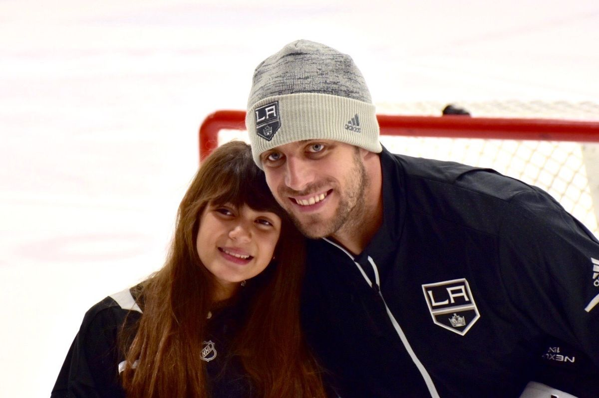 Christiann from Make-A-Wish Foundation poses for a photo with LA Kings Captain Anze Kopitar on the ice at Toyota Sports Performance Center.