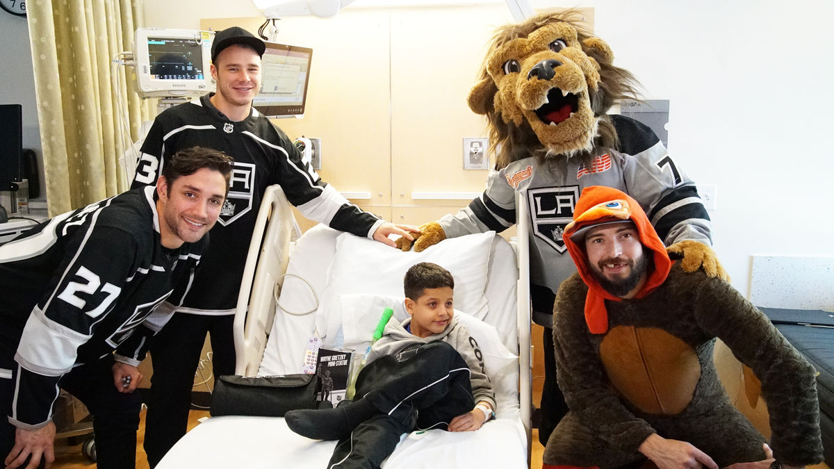 LA Kings Players Alec Martinez, Dustin Brown, Drew Doughty and LA Kings Mascot pose for a photo with a young male patient at Children's Hospital Los Angeles.