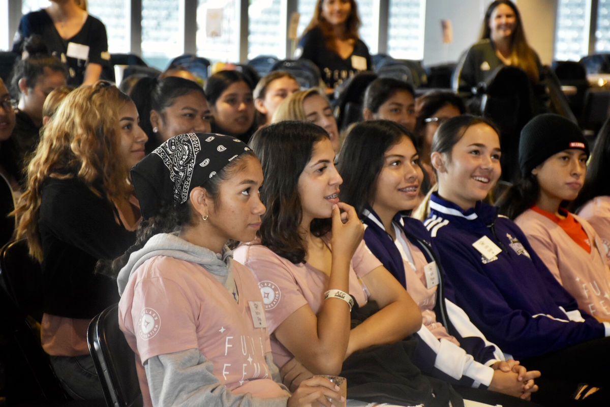 High school female athletes laugh in the audience during a panel at the second Annual LA Galaxy High School Girls' Summit at Dignity Health Sports Park.