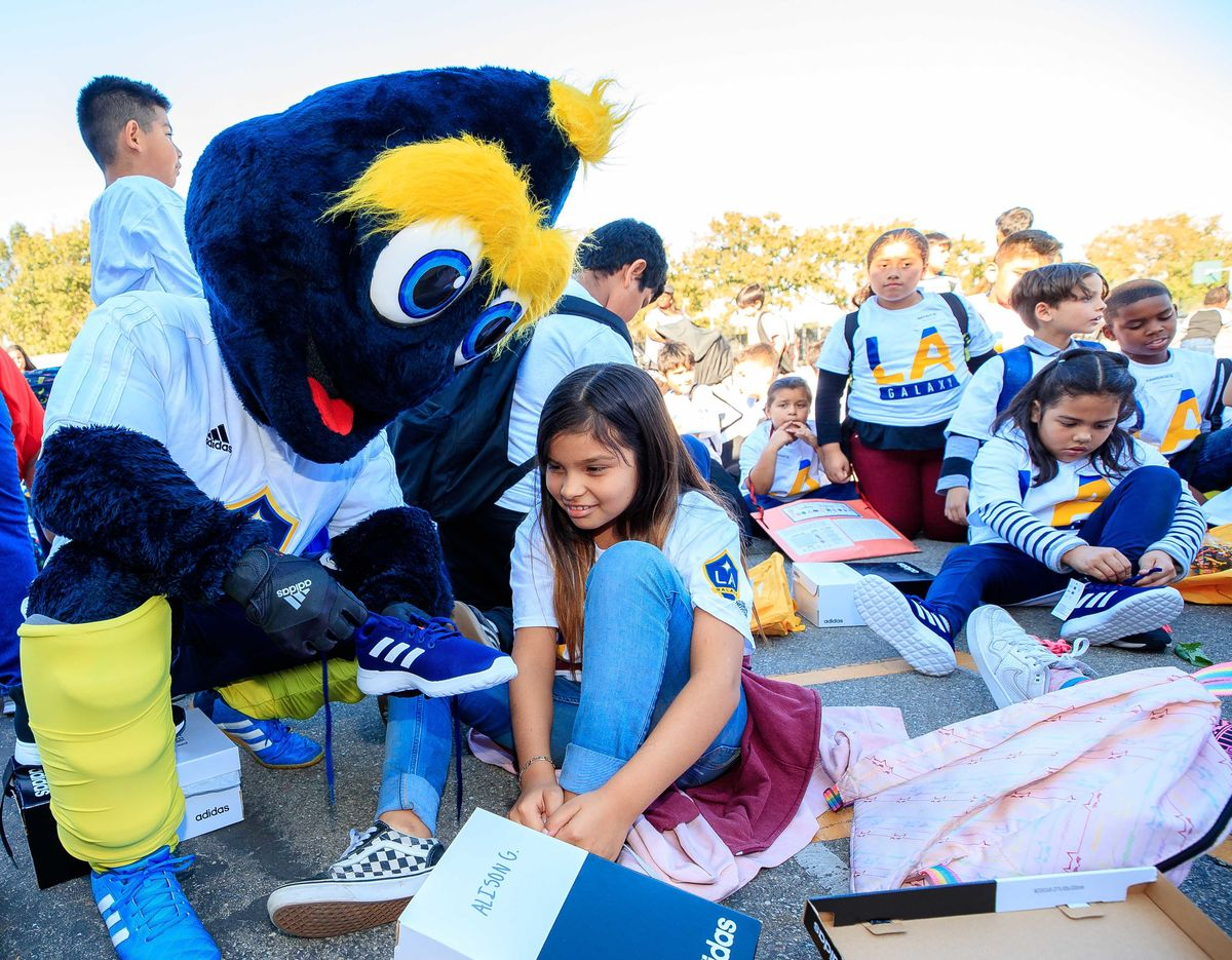 LA Galaxy mascot Cozmo helps a young girl put on a brand new pair of running shoes, surrounded by other students putting shoes on.
