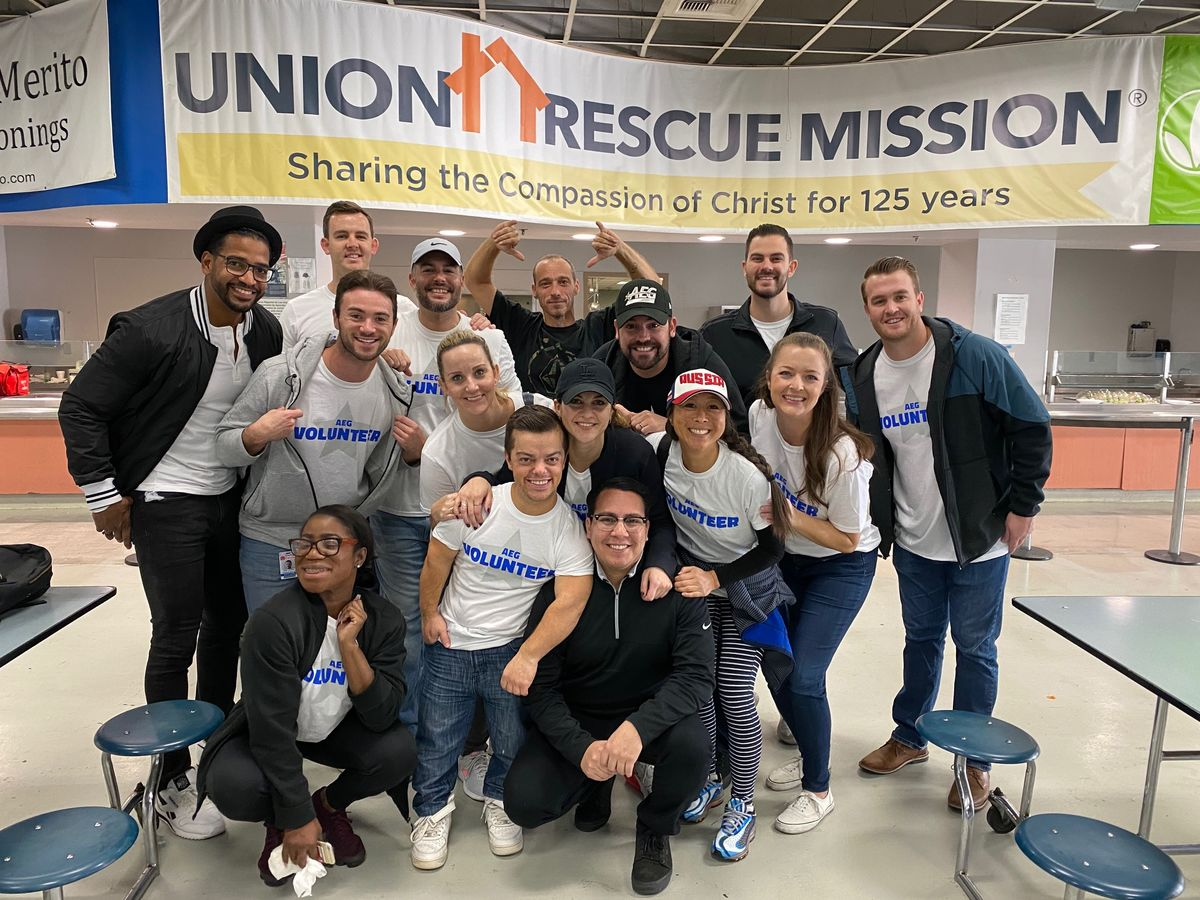 "Employees in white AEG volunteer shirts gather in front of a banner that reads ""Union Rescue Mission"" after volunteering to prepare and serve breakfast."