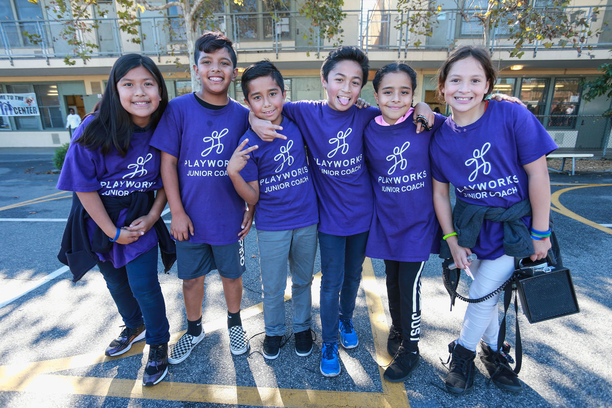 Six elementary school students and Playworks junior coaches in purple shirts gather together for a group photo on the playground.