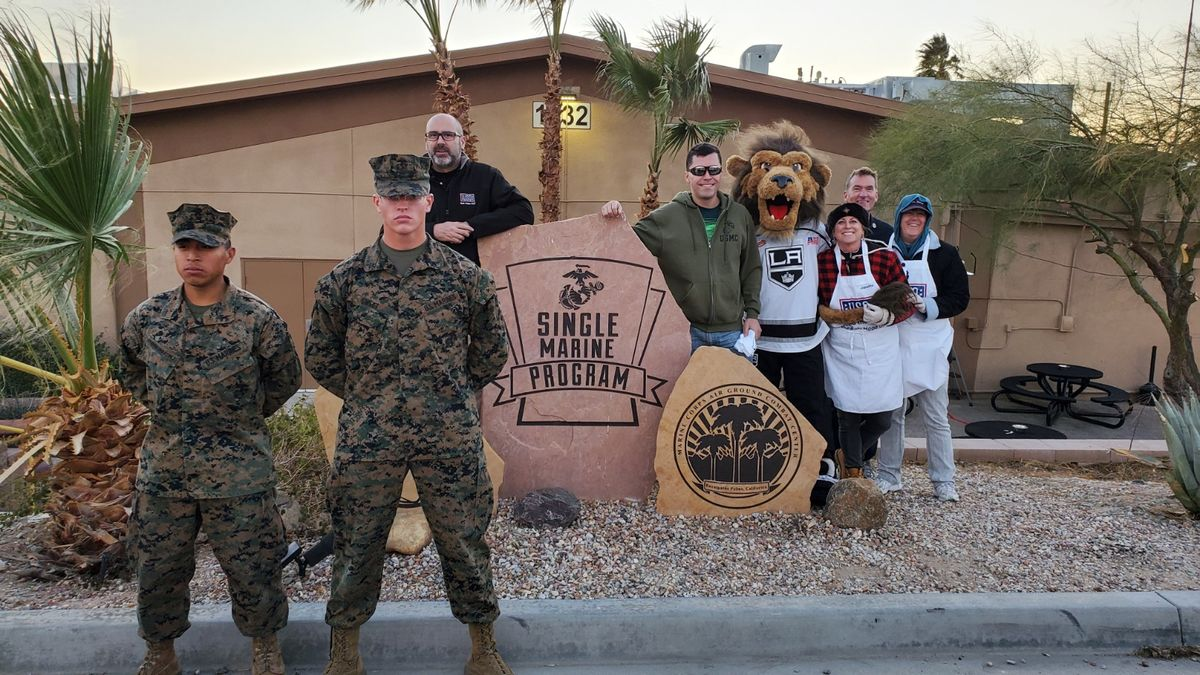Two marines stand at attention in with LA Kings mascot Bailey and members of the USO during a watch party at the military training facility Twentynine Palms for Marines.