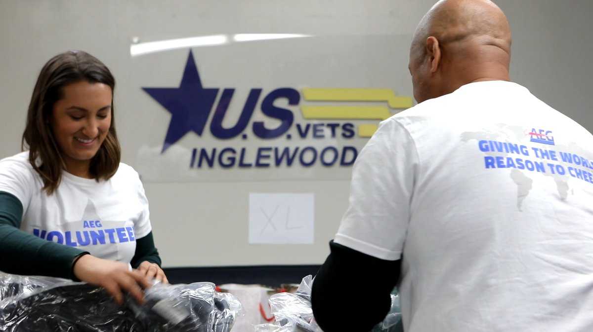 Two AEG volunteers in AEG volunteer shirts sort clothes in front of a U.S. Vets Inglewood sign.