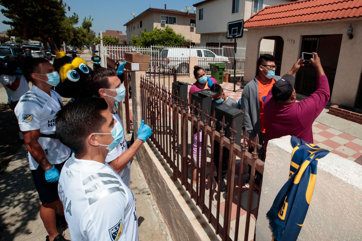 LA Galaxy players wearing jerseys and masks pose for a socially distant photo with a family in Los Angeles.