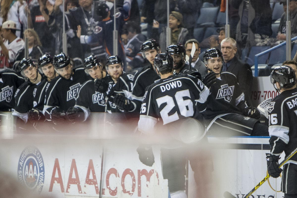 Reign players on the bench exchanging high fives with a player on the ice