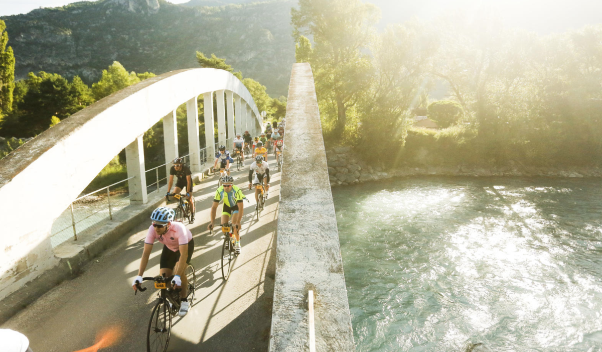 Riders biking over a bridge