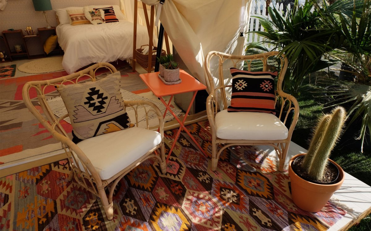 Image of two chairs with a bed in the background decorated in tribal print under a tent similar to a teepee