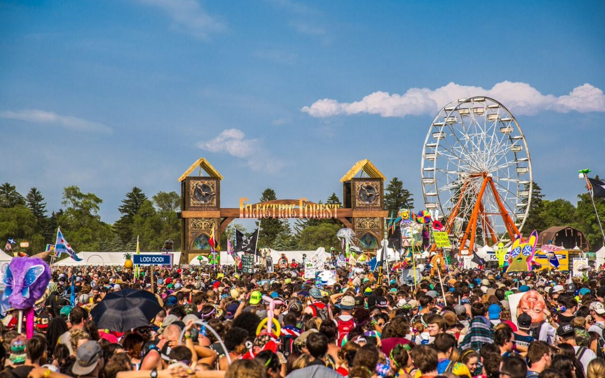 Image of the crowd at electric forest during the day with the ferris wheel in the back