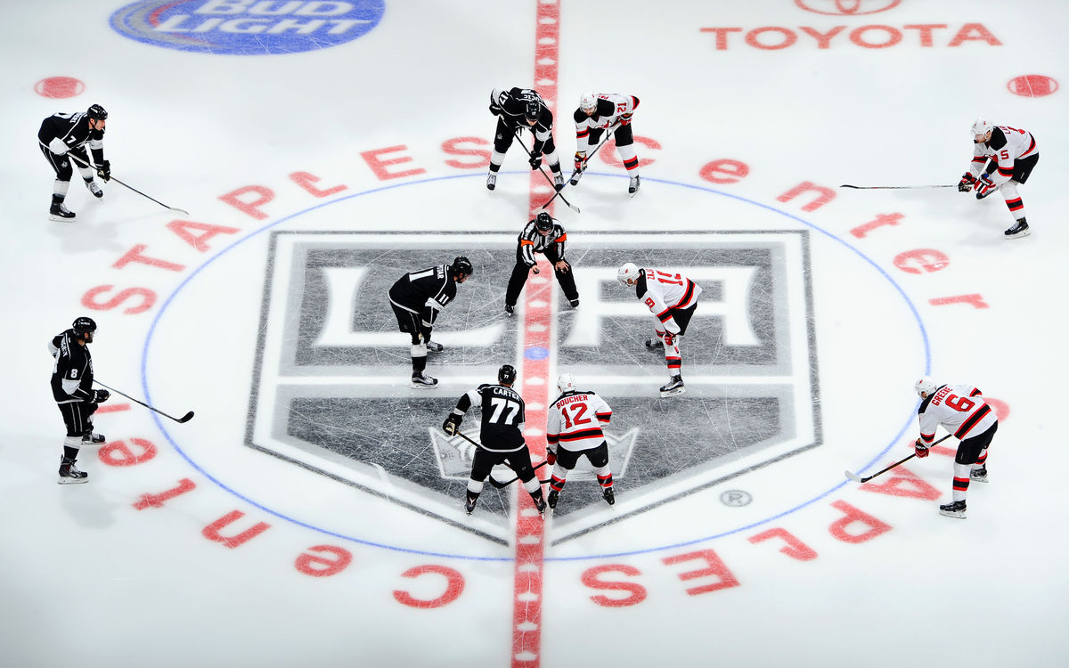 LA Kings players face off against an opposing team for the puck drop at STAPLES Center.