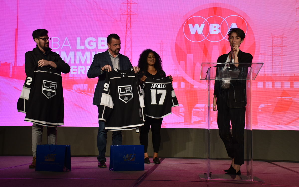 Emma Toshack (right), one of the founders of Nomadica, the business selected to participate in AEG's Inaugural Capacity Building Program, is presented with personalized LA Kings jerseys from members of AEG at the WBA LGBT Economic Impact Summit on March 15, 2019.