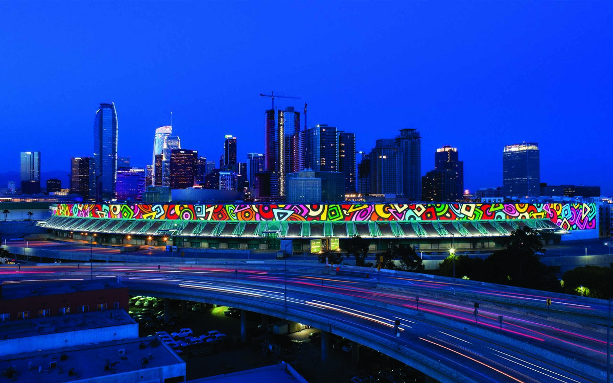 The Portraits of Hope art installation on the South Hall of the Los Angeles Convention Center is illuminated at night as cars pass by on the freeway.
