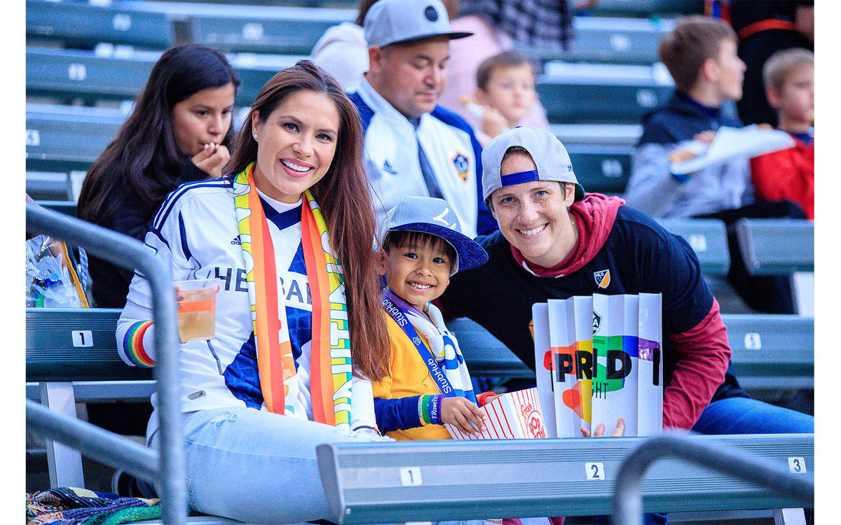 Fans smile for a photo in the stands of the LA Galaxy's Pride Night at Dignity Health Sports Park.