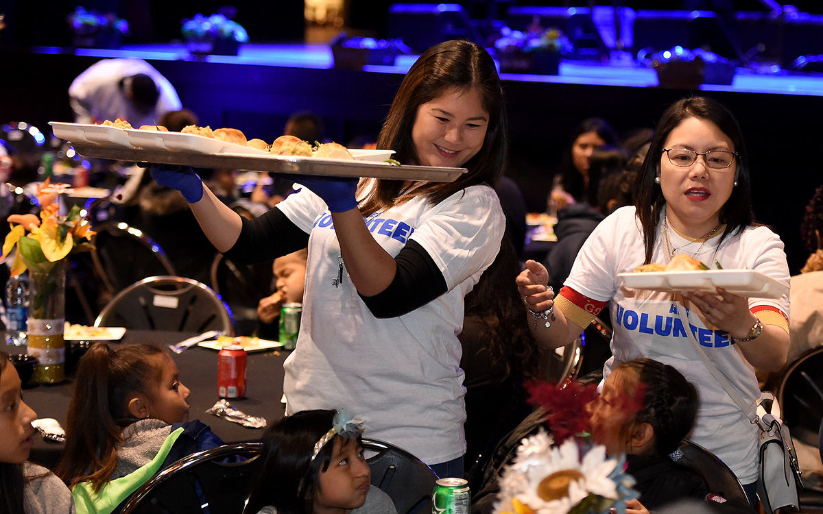 Two female AEG employees serve plates of food from a tray to families at the AEG Thanksgiving Celebration at L.A. LIVE's The Novo.
