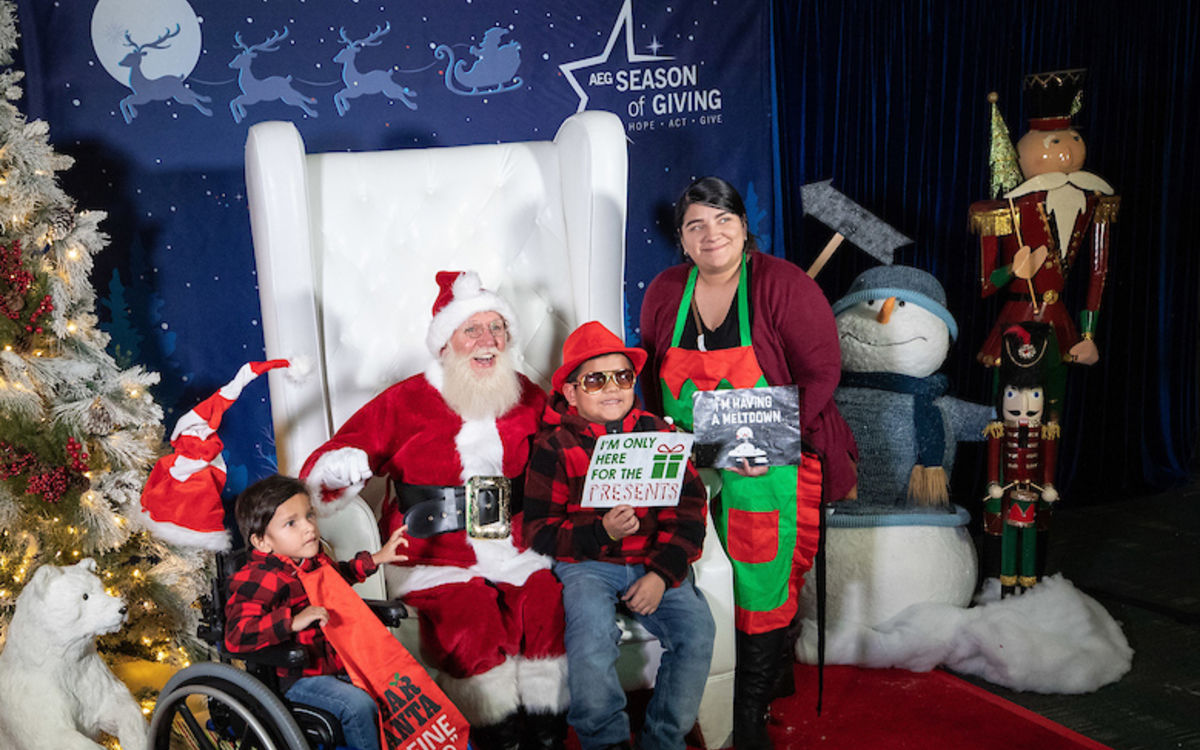 Two boys and a mother pose with Santa during AEG's annual Community Holiday Party at the Los Angeles Convention Center.