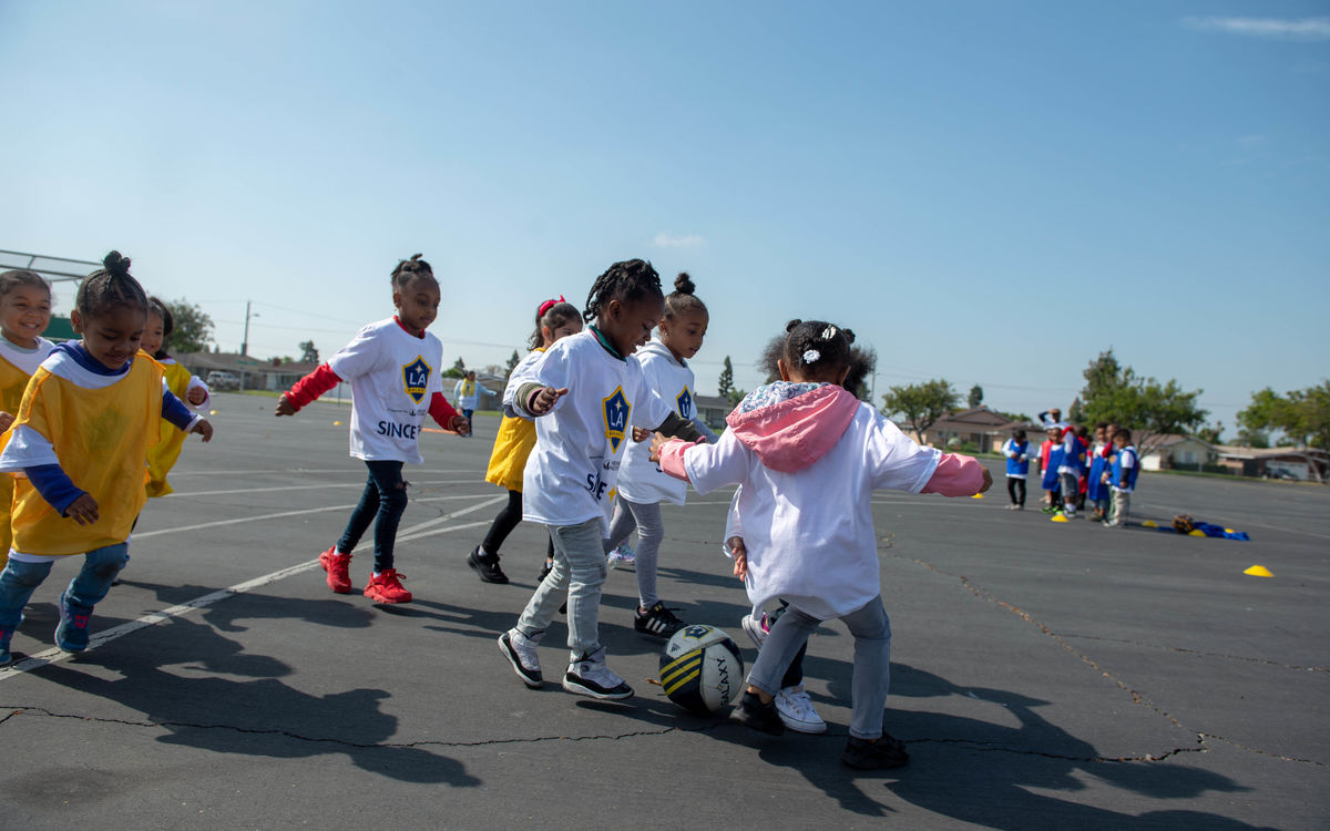 A group of small children run after a soccer ball on the blacktop at school during an LA Galaxy Youth Soccer Clinic hosted by the LA Galaxy Foundation.